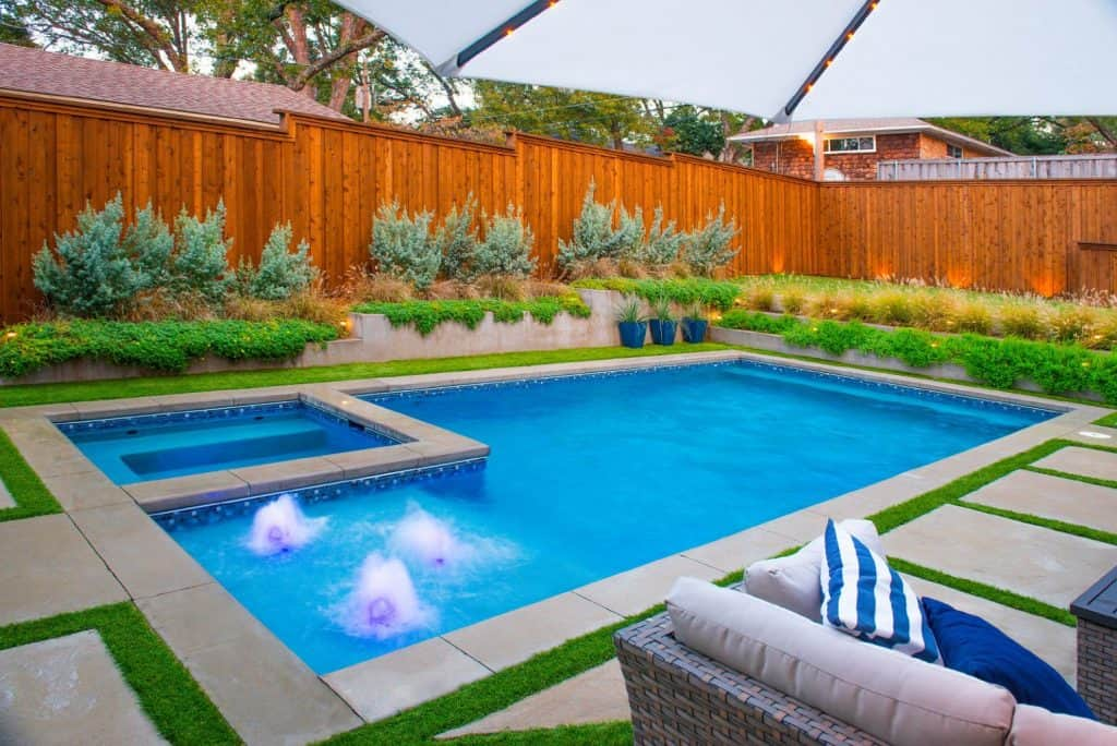 Beautiful rectangulr outdoor swimming pool with nice fence and landscaping