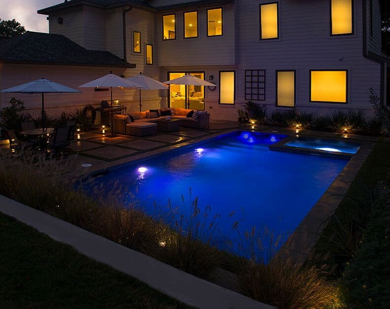 Well lit rectangular backyard swimming pool with nice patio furniture on the porch