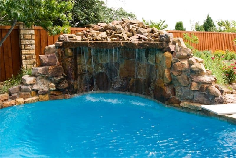 Custom stone grotto waterfall feature in a backyard pool