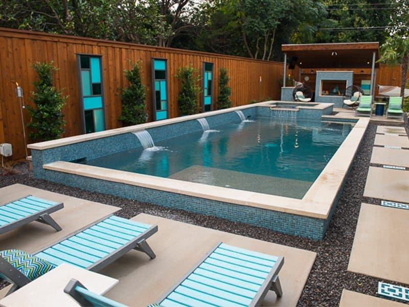 Backyard rectangle pool with water fountain feature and lounge chairs