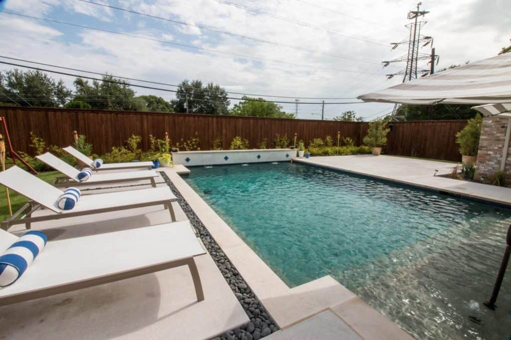 Nice rectangle swimming pool with a row of lounge chairs