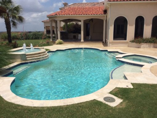 Beautiful oval pool in the backyard of a Spanish style home