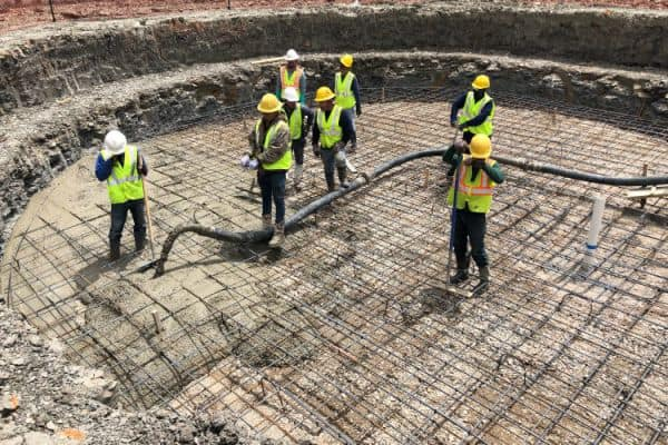8 workers are shown pouring the concrete base of a pool under the steel rebar