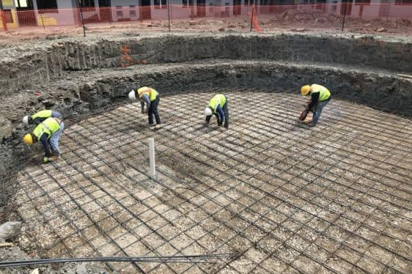Four construction workers stand in a pool that's being built, tying the rebar