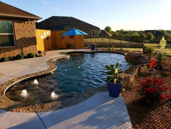 Freeform pool with an umbrella table and three bubblers surrounded by landscaping and an iron fence