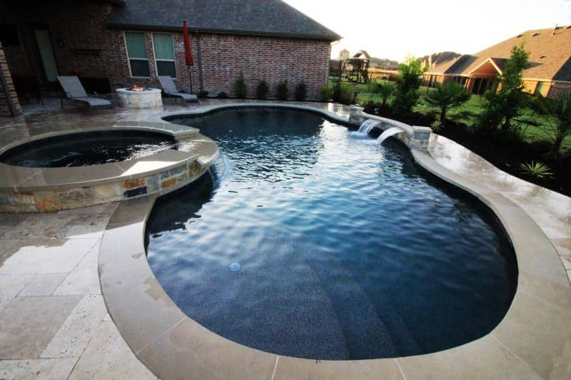 Custom free form swimming pool in backyard with Jacuzzi waterfall