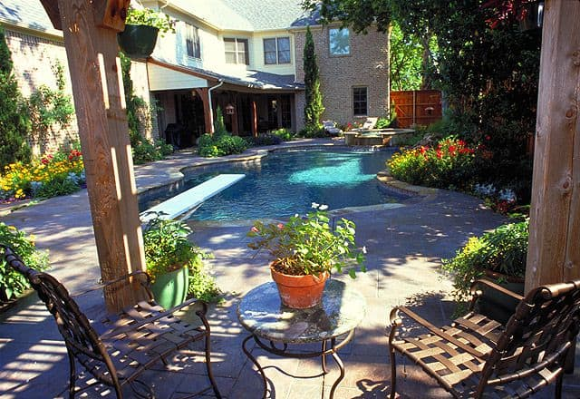 Full view of a backyard with a pool and deck with chairs surrounded by landscaping