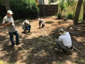 Four men measure for a pool build