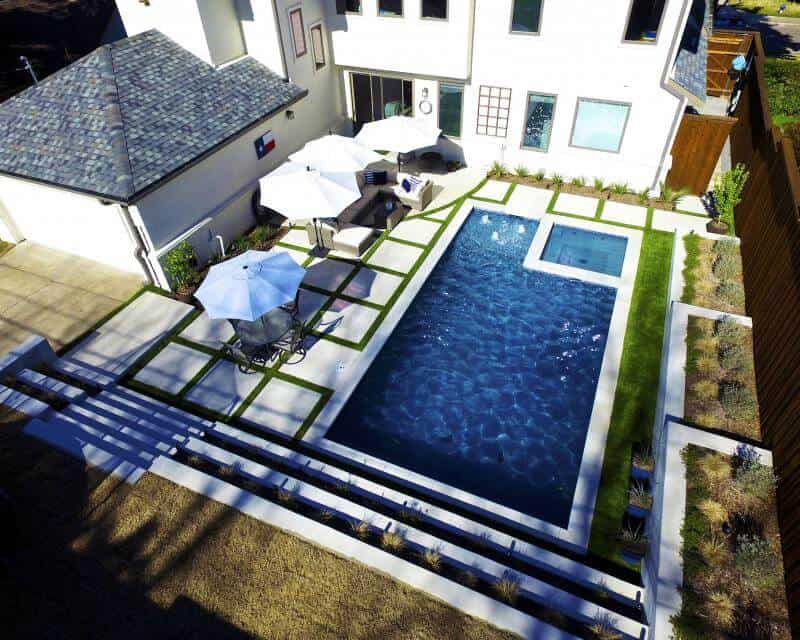 Ariel view of a backyard pool surrounded by a white house