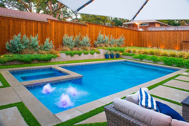 Rectangle pool surrounded by a privacy fence and landscaping