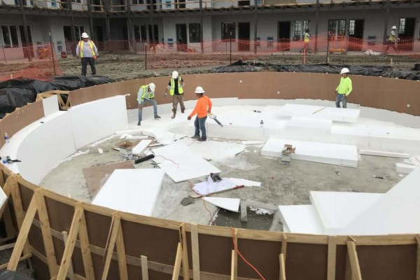Four construction workers stand within a pool being constructed among sheets of geofoam