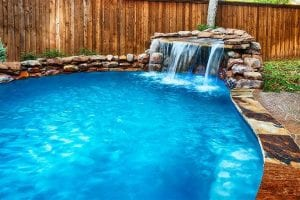 A beautiful waterfall over a free-form pool.