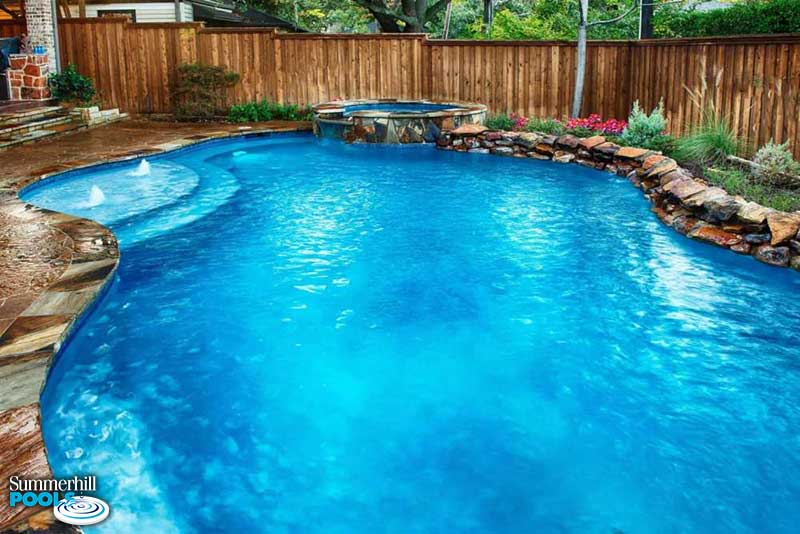 free form pool with rock ledges and spa