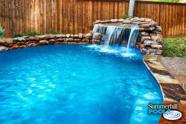 rock waterfall into a residential pool