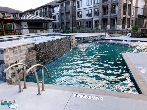 apartment complex pool with tile waterfall